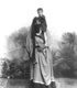 Click to see details of a veiled woman carrying a child on her...
